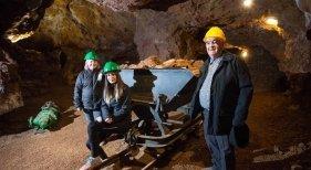 Un antiguo trabajador de la mina junto a su nieta Marta Bellés y Sandy, ambas guías