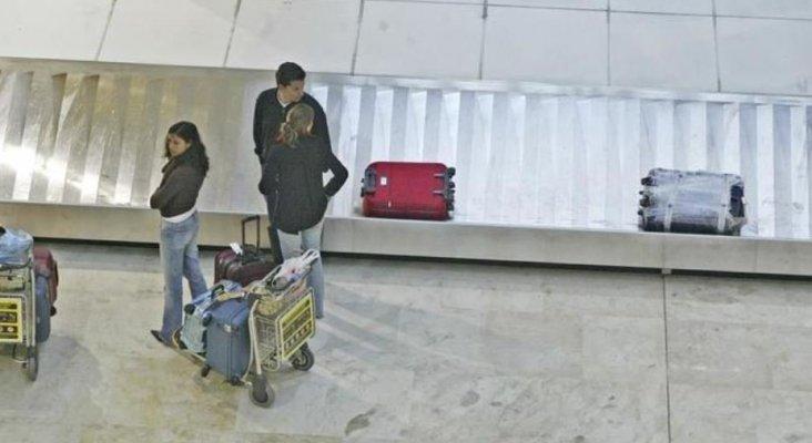 Pasajeros esperan por sus maletas en el aeropuerto de Madrid-Barajas