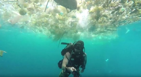 Buceador nadando entre plástico