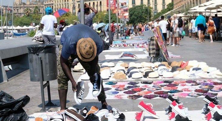 El top manta invade zonas turísticas de España|Foto: vendedores ambulantes en el Puerto de Barcelona- Marga Cruz vía El Mundo