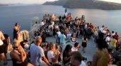 Turistas apreciando el atardecer en Santorini