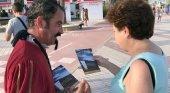 Un actor que representa a Cervantes entrega un folleto a una visitante en Vélez-Málaga