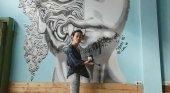 Luanna Lee junto a una de sus obras en un albergue en Bangkok